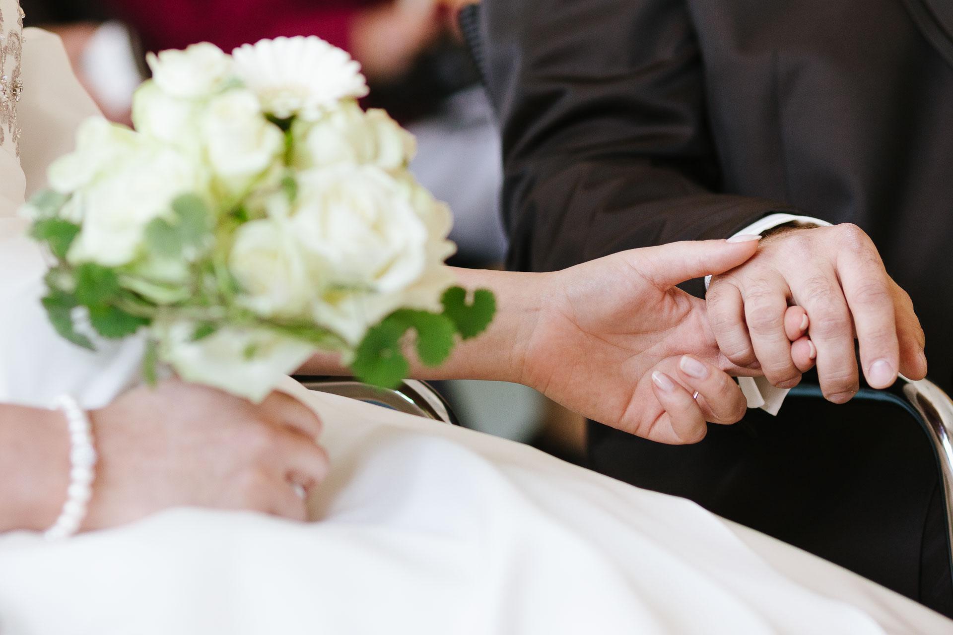 Brautstrauß mit den Händen des Paares